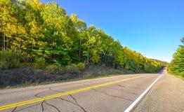 De open weg van de de zomerweg aan overal Zonnige blauwe hemel, hout aan beide kanten onderaan een weg van het land in de zomer Stock Foto