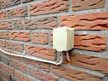 De openlucht elektrocontactdoos wordt opgezet op de bakstenen muur stock afbeeldingen