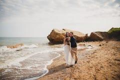 De openluchtceremonie van het strandhuwelijk dichtbij het overzees, de modieuze gelukkige glimlachende bruidegom en de bruid kuss Stock Foto