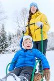 De openluchtgangen van het portretmamma met de zoon in de winter Zij carr royalty-vrije stock afbeelding