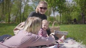 De openluchtrecreatie van de portretfamilie Twee mooie jonge moeders en hun kinderen bij een picknick in het park Een jongen en a stock video