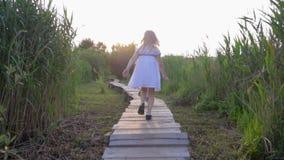 De openluchtspelen, het actieve gezonde kindmeisje en het jongensspel lopen en lopen op houten brug in aard onder groen gras de a stock footage