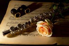 De operaglazen, zilveren fluit en geel namen op een oude muziekscore toe Stock Foto's