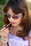 De opgedirkte tiener past lippenstift toe Stock Foto's