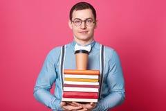 De opgetogen bepaalde student stelt geïsoleerd over roze achtergrond in studio, die blauw overhemd, witte bowtie, gestreepte bret royalty-vrije stock foto