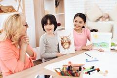 De opgetogen grootmoeder bekijkt tekeningen van kleinkinderen Weinig jongen trok uil op blad Meisje geschilderd landschap stock fotografie