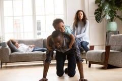 De opgewekte Afrikaanse Amerikaanse jonge papa die van de peuterrit samen spelen stock afbeelding