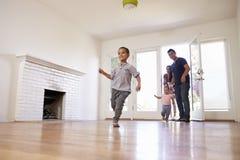 De opgewekte Familie onderzoekt Nieuw Huis bij het Bewegen van Dag Royalty-vrije Stock Fotografie