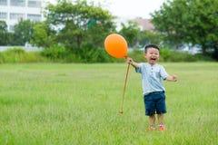 De opgewekte greep van de Babyjongen met oranje ballon Royalty-vrije Stock Afbeelding