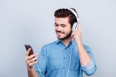 De opgewekte jonge knappe mens luistert aan muziek op zijn pda met royalty-vrije stock afbeelding