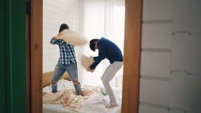De opgewekte jonge man en de vrouw hebben hoofdkussens bestrijden en pret die thuis dan koesterend en kussend lachen huizen stock video