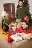 De opgewekte jongen met familie en stelt bij Kerstmis voor Stock Foto's