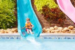 De opgewekte kinderen in water parkeren het berijden op dia met vlotter royalty-vrije stock foto's