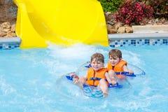 De opgewekte kinderen in water parkeren het berijden op dia met vlotter royalty-vrije stock fotografie