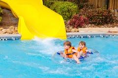 De opgewekte kinderen in water parkeren het berijden op dia met vlotter stock foto