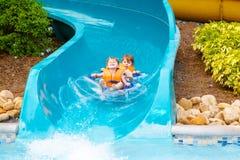 De opgewekte kinderen in water parkeren het berijden op dia met vlotter stock afbeeldingen