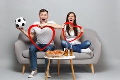 De opgewekte de man van de paarvrouw voetbalfans juichen steun omhoog favoriet team met voetbalbal toe, greep grote rode houten h stock afbeelding