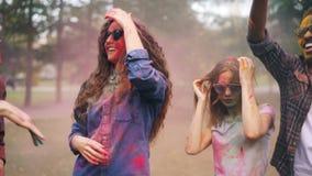 De opgewekte mannen en de vrouwen dansen bij partij die omvat met heldere verf van traditionele Indische vakantie Holi genieten d stock videobeelden