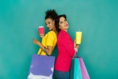 De opgewekte meisjes met het winkelen zakken en halen dranken weg Royalty-vrije Stock Foto