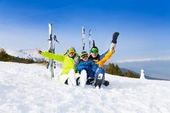 De opgewekte ouders en het jonge geitje in skimaskers zitten op sneeuw Stock Afbeeldingen