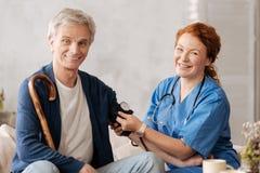 De opgewekte vrolijke verpleegsterslezing bemant bloeddruk royalty-vrije stock foto