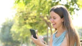 De opgewekte vrouw vindt online aanbiedingen op smartphone stock videobeelden