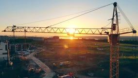 De opheffende kraan bevindt zich in het de bouwgebied Concept 6 van onroerende goederen Bouwwerf bij zonsondergang stock footage