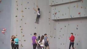 De opleiding van jonge atleten bij de het beklimmen muur Groep klimmers die bij binnenrotsgymnastiek praktizeren stock footage