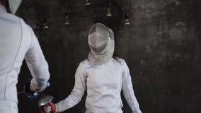 De opleiding van twee jonge schermers in een sportenschool, sluit omhoog van hoofd en folies stock footage