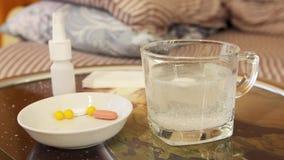 De oplosbare witte tablet lost in glas met water op stock videobeelden