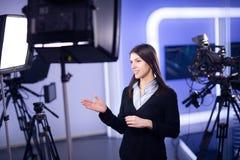 De opname van de televisiepresentator in nieuwsstudio Vrouwelijk journalistanker die bedrijfsrapport voorleggen, die in televisie Stock Afbeeldingen