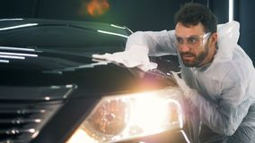 De oppervlakte van de auto wordt door een werknemer met een doek wordt schoongemaakt die stock videobeelden