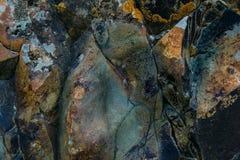 De oppervlakte van een oude rots met barsten en mos De oude wilde achtergrond van de rotstextuur stock foto