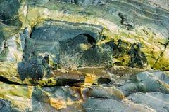 De oppervlakte van een oude rots met barsten De oude wilde achtergrond van de rotstextuur stock afbeelding