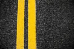 De oppervlakte van het wegasfalt met twee gele lijnen Royalty-vrije Stock Foto