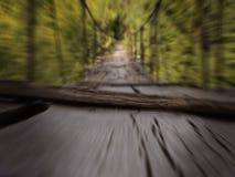 De opschortings houten brug door de rivier in het bos royalty-vrije stock foto