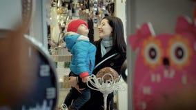 In de opslag, houdt de moeder een jonge zoon in haar wapens stock videobeelden