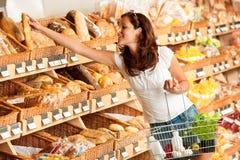 De opslag van de kruidenierswinkel: Jonge vrouwenholding het winkelen mand Royalty-vrije Stock Fotografie