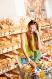 De opslag van de kruidenierswinkel: Rode haarvrouw met mobiele telefoon Royalty-vrije Stock Afbeelding