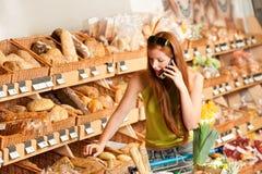 De opslag van de kruidenierswinkel: Rode haarvrouw met mobiele telefoon Stock Afbeelding