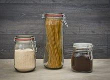 De opslag van het voedsel Voedselingrediënten in glaskruiken, op houten achtergrond Stock Foto's