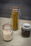 De opslag van het voedsel Voedselingrediënten in glaskruiken, op houten achtergrond royalty-vrije stock afbeeldingen