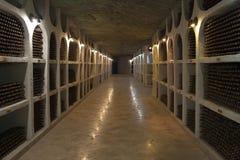 De opslag van wijnflessen in een wijnkelder Stock Foto