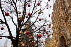 De opslaggom op de achtergrond van bomen met Kerstmisballen die worden verfraaid Rood vierkant nacht Moskou, Rusland Stock Afbeeldingen