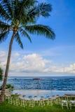De opstelling van de huwelijksceremonie dichtbij de oceaan bij zonsondergang - krukken voor gasten onder de palm royalty-vrije stock foto's