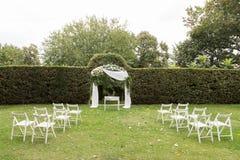 De opstelling van de huwelijksceremonie Huwelijksboog en witte stoelen op groen gazon in de tuin Stock Fotografie