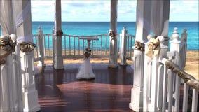 De opstelling van huwelijksgazebo voor een burgerlijke ceremonie in een tropische kusttuin op een Caraïbisch eiland stock footage