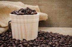 De opstelling van koffiebonen op houten vat en rustieke achtergrond Stock Foto