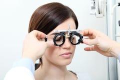 De opticien met proefkader, optometrist arts onderzoekt zicht stock afbeelding