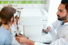 De Optometrist Testing Woman Eyesight van de oogtest op Modern Materiaal stock fotografie